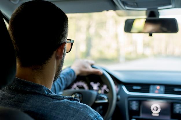 Hombre irreconocible conduciendo coche en carretera vacía Foto gratis