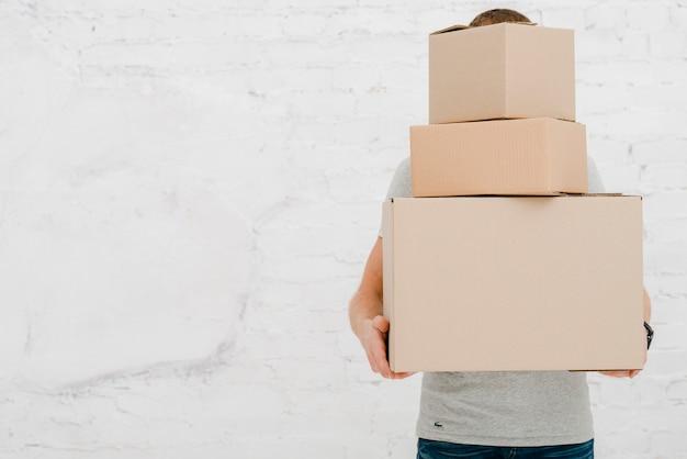 Hombre irreconocible llevando cajas Foto gratis