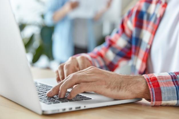 Hombre irreconocible trabaja en una computadora portátil portátil moderna, instala una nueva aplicación Foto gratis