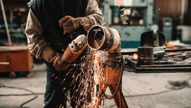 Hombre irreconocible en traje de protección y guantes de corte de tubería con amoladora. interior del taller. Foto Premium