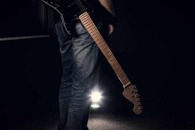 Un hombre en jeans sosteniendo su guitarra eléctrica sobre fondo negro Foto Premium