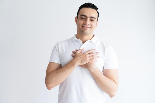 Hombre joven agradecido que mantiene las manos en el pecho y que mira la cámara. Foto gratis
