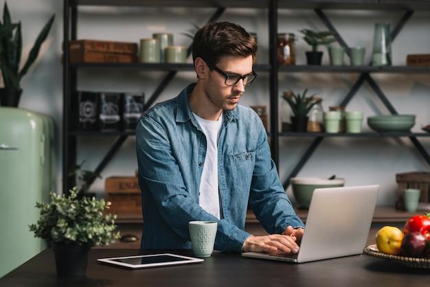 Hombre joven con anteojos usando laptop en cocina Foto gratis