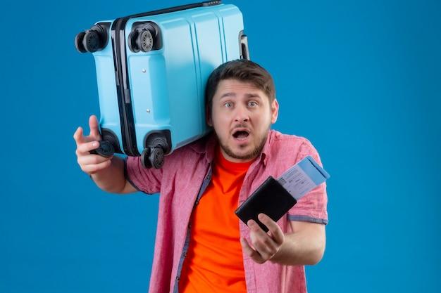 Hombre joven apuesto viajero molesto que sostiene la maleta y los billetes de avión que parecen confundidos muy emocionales y preocupados de pie sobre la pared azul Foto gratis