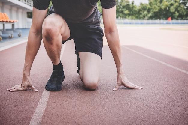 Hombre joven atleta de fitness preparándose para correr en pista, concepto de bienestar ejercicio entrenamiento Foto Premium