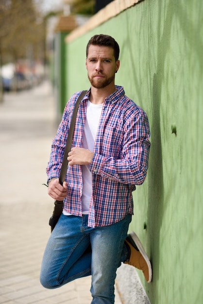 Hombre joven atractivo que se coloca en fondo urbano. concepto de estilo de vida Foto Premium