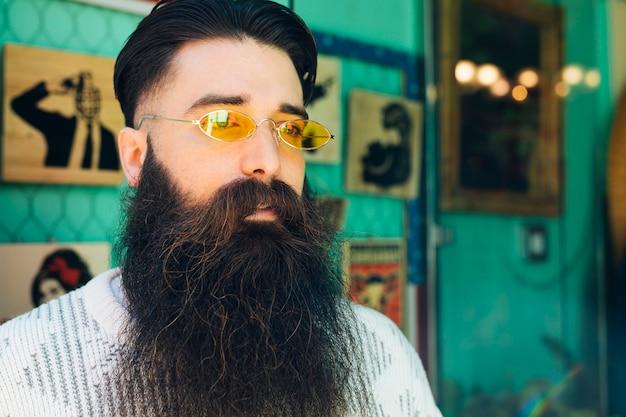 Hombre joven de la barba hermosa con las lentes amarillas que miran lejos Foto gratis