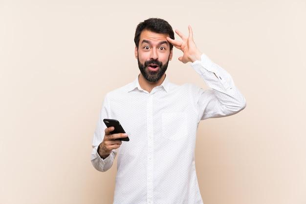 Un hombre joven con barba sosteniendo un móvil acaba de darse cuenta de algo y tiene la intención de encontrar la solución Foto Premium
