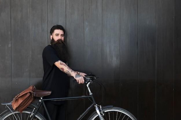 Hombre joven barbudo con su bicicleta frente a una pared de madera negra Foto gratis