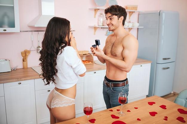 Un hombre joven y bien parado se para en la cocina y hace la posposición a la mujer. ella se ve feliz y emocionada. guy mantenga el anillo en la caja delante de la mujer. Foto Premium