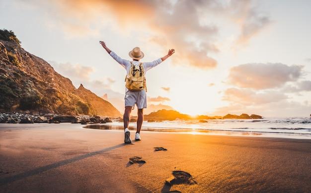 Hombre joven con los brazos extendidos junto al mar al amanecer disfrutando de la libertad y la vida, la gente viaja concepto de bienestar Foto Premium