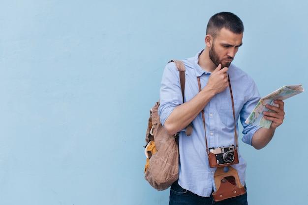 Hombre joven con la cámara alrededor de su cuello leyendo el mapa sobre fondo azul Foto gratis