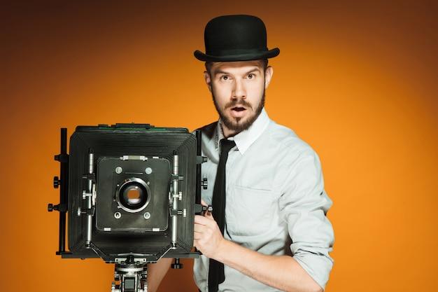 Hombre joven con cámara retro Foto gratis