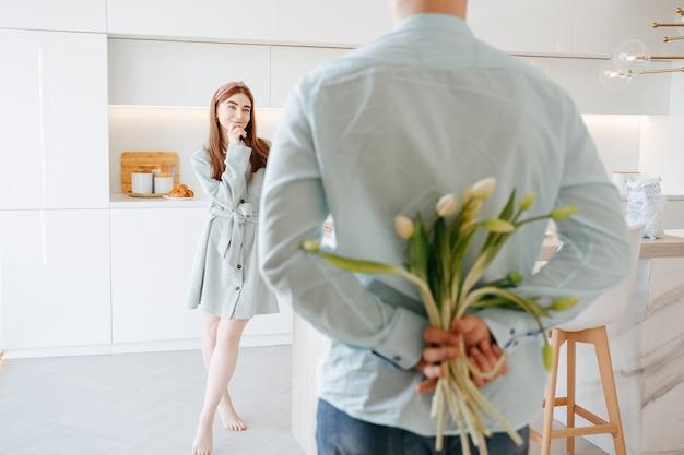 Un hombre joven con una camisa ligera sostiene un ramo de tulipanes como regalo para su esposa a sus espaldas en casa. primer plano de flores el 8 de marzo. lugar libre. Foto Premium