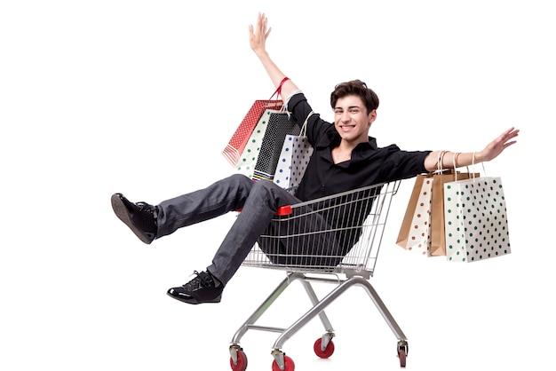 Hombre joven con el carro y los bolsos de compras aislados en blanco Foto Premium