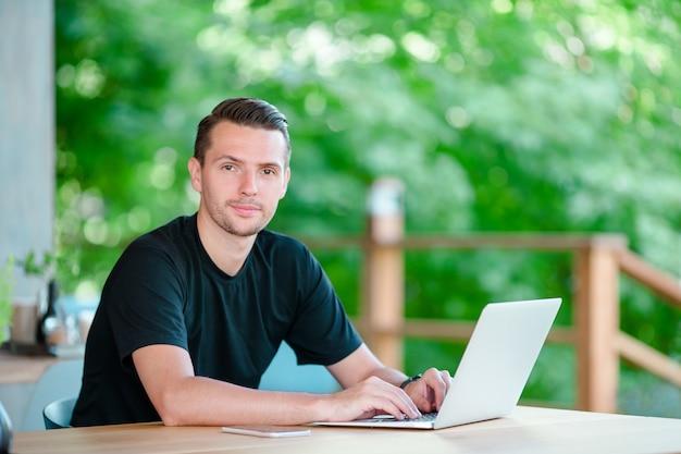 Hombre joven con la computadora portátil en café al aire libre que bebe el café. hombre con teléfono inteligente móvil. Foto Premium
