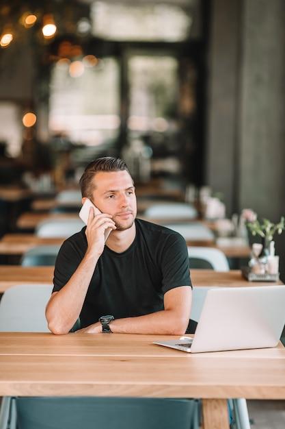 Hombre joven con la computadora portátil en café al aire libre que bebe el café. Foto Premium