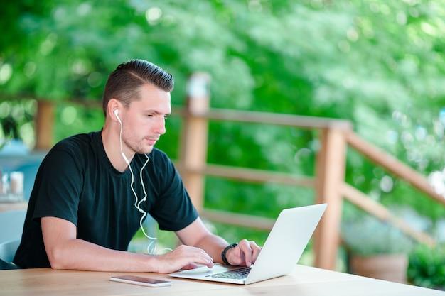 Hombre joven con la computadora portátil en café de consumición del café al aire libre. hombre que usa teléfono inteligente móvil. Foto Premium