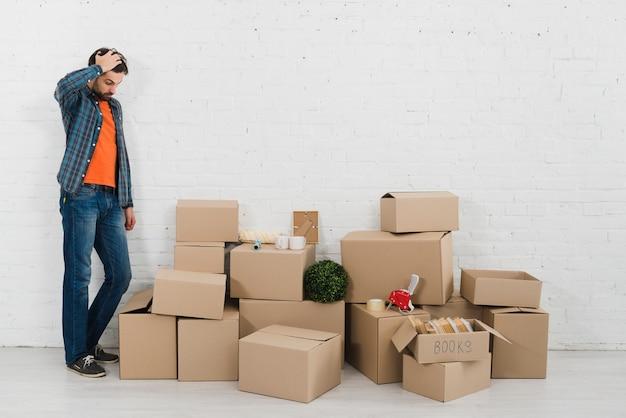 Hombre joven confuso que mira pilas de cajas de cartón contra la pared de ladrillo blanca Foto Premium