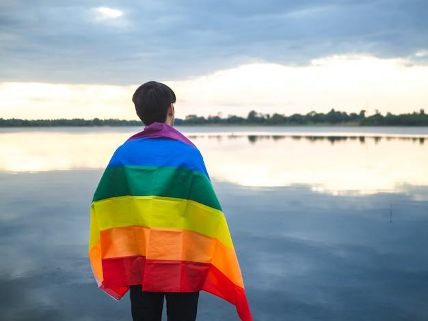 Hombre joven cubierto por una bandera del arco iris al lado del lago en fondo del cielo de la puesta del sol. Foto Premium