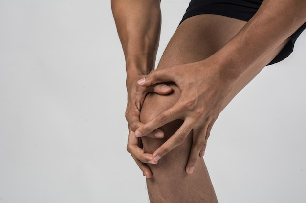 Hombre joven del deporte con las piernas atléticas fuertes que sostienen la rodilla con sus manos en dolor después de sufrir lesión del ligamento aislada en blanco. Foto gratis