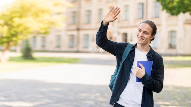 Hombre joven con estilo feliz de volver a la universidad Foto gratis