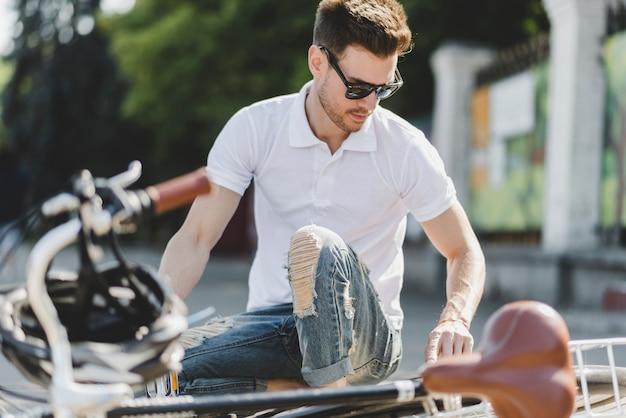 Hombre joven con estilo que repara la bicicleta en el camino Foto gratis