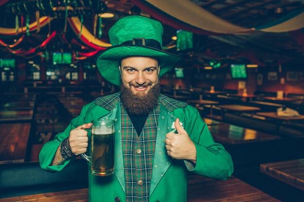 Hombre joven feliz y positivo en traje verde en pub. sostiene una jarra de cerveza y muestra el pulgar hacia arriba. el joven está satisfecho. Foto Premium