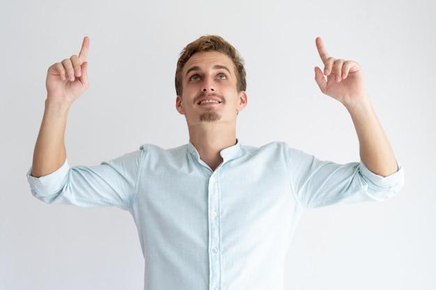 Hombre joven feliz que señala y que mira hacia arriba Foto gratis