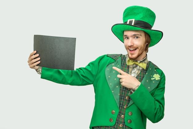 Hombre joven feliz en traje verde con trozo de papel negro. viste el traje de san patricio. aislado en gris Foto Premium