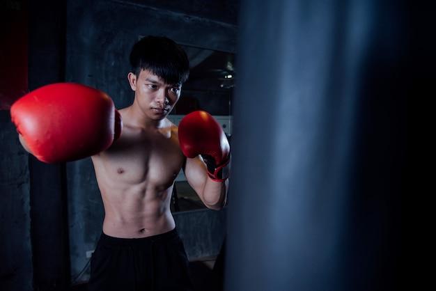 Hombre joven fuerte deportes hombre boxeador hacer ejercicios en el gimnasio, concepto saludable Foto gratis