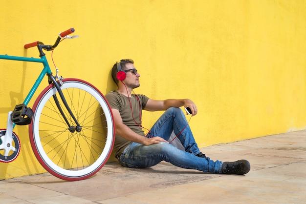 Hombre joven con gafas de sol relajantes en el suelo y escuchando música. sentado contra una pared amarilla con su computadora Foto Premium