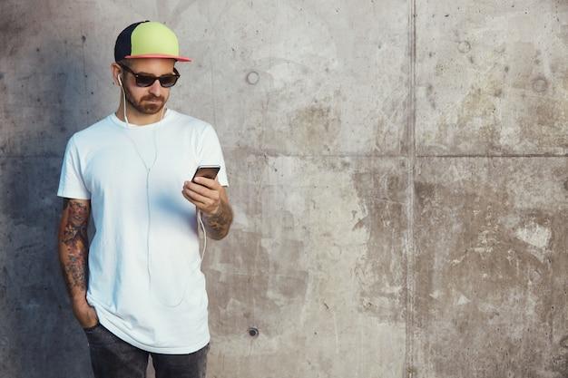 Hombre joven con gorra de béisbol, gafas de sol y camiseta blanca en blanco leyendo algo en su teléfono inteligente de pie junto a un muro de hormigón gris Foto gratis