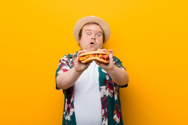 Hombre joven de gran tamaño con un hot dog contra la pared plana Foto Premium