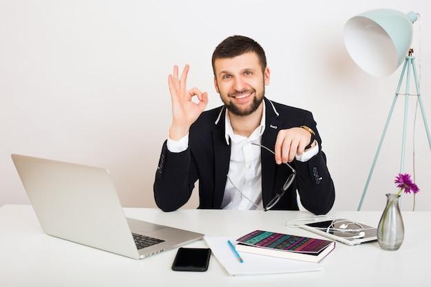 Hombre joven guapo con estilo hipster en chaqueta negra en la mesa de oficina, estilo empresarial, camisa blanca, aislado, trabajando en la computadora portátil, puesta en marcha, lugar de trabajo, sonriente, feliz, positivo, Foto gratis