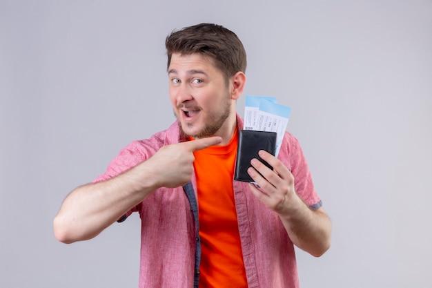 Hombre joven guapo viajero sosteniendo billetes de avión apuntando con el dedo a ellos sonriendo alegremente positivo y feliz de pie sobre la pared blanca Foto gratis