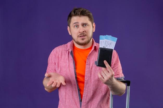 Hombre joven guapo viajero sosteniendo billetes de avión mirando confundido Foto gratis