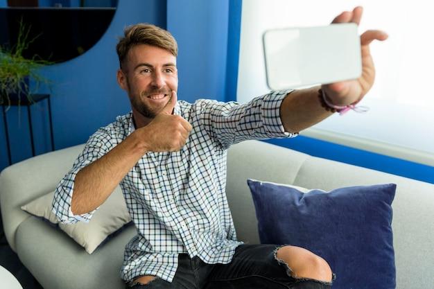 Hombre joven haciéndose un selfie Foto gratis