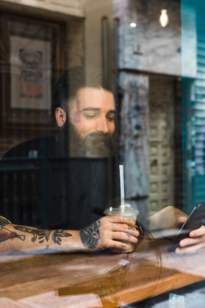 Hombre joven hermoso que se sienta en café usando el teléfono móvil Foto gratis