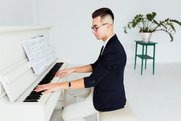 Hombre joven hermoso que toca el piano mirando la hoja musical Foto gratis