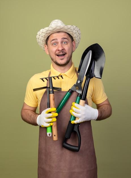 Hombre joven jardinero vestido con mono y sombrero en ...