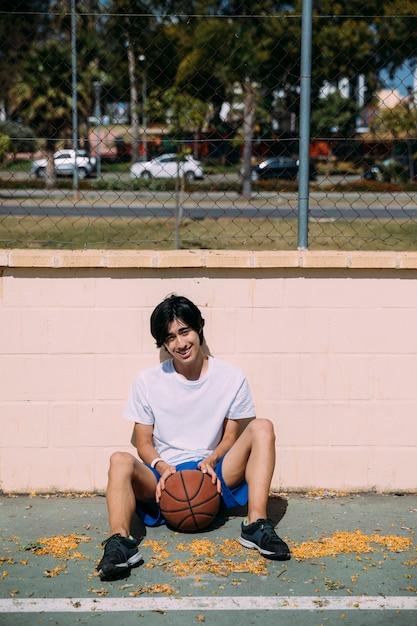 Hombre joven juguetón que se sienta en el asfalto con baloncesto al aire libre Foto gratis