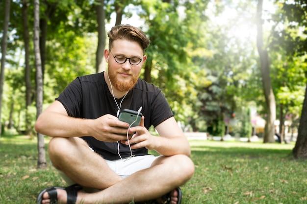 Hombre joven lindo pelirrojo barbudo en auriculares escuchando música en un teléfono inteligente mientras está sentado en un parque. Foto Premium