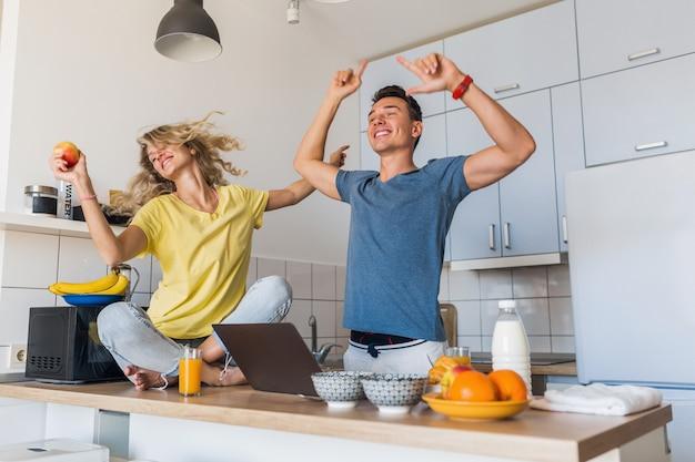 Hombre joven y mujer enamorada divirtiéndose saludable desayuno en la cocina por la mañana Foto gratis