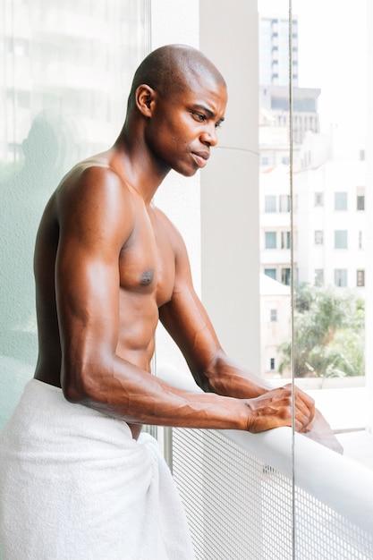 Hombre joven muscular descamisado hermoso con la toalla que se coloca en el balcón Foto gratis