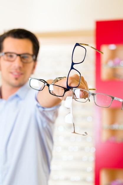Hombre joven en óptica con gafas Foto Premium