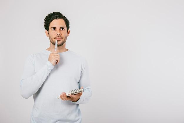 Hombre joven pensando con libreta y bolígrafo Foto Premium