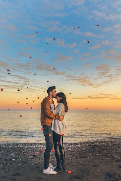 Hombre joven que besa a la mujer en la frente en orilla de mar Foto gratis