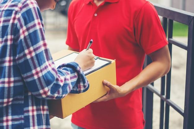 Hombre joven que entrega el paquete al cliente en casa. entrega Foto gratis