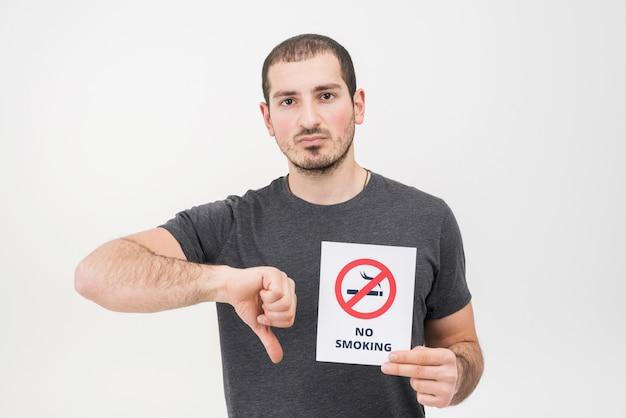 Un hombre joven que lleva a cabo la muestra de no fumadores que muestra los pulgares hacia abajo contra el fondo blanco Foto gratis